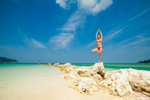 Hot summer yoga session on a beach - tropical Koh Phangan island, Thailand. Vriksha-asana - tree pose.